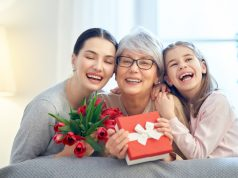 """Alt=""""Happy mother's day! Child and mom congratulating granny giving her flowers tulips ang gift box. Grandma, mum and girl smiling and hugging. Family holiday and togetherness."""""""