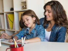 "alt=""Young woman with little girl using computer at home, self isolating"""