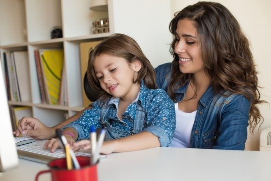 """alt=""""Young woman with little girl using computer at home, self isolating"""""""